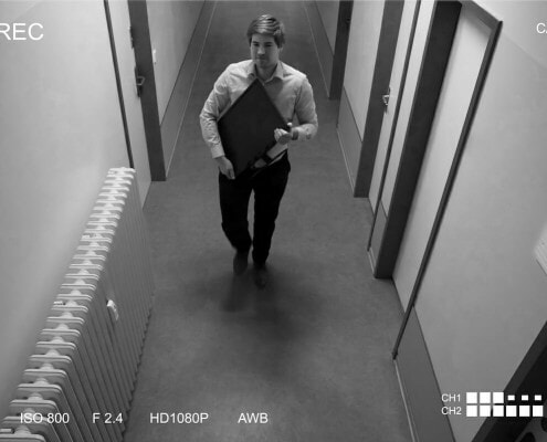 Black and white photo of thief: Young Man Stealing Computer Monitor Walking In Corridor Scene Through CCTV Camera