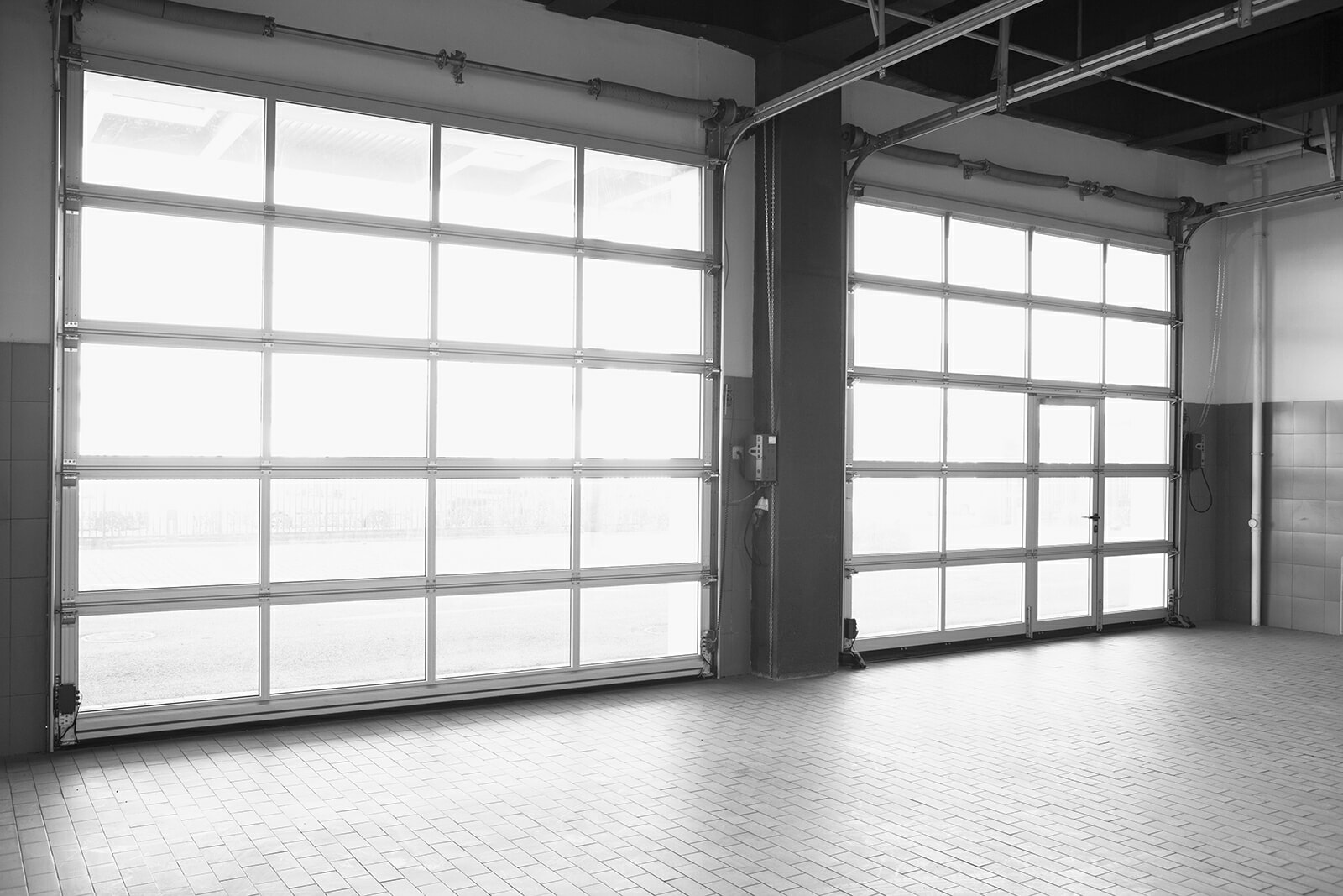 Inside an empty mechanic garage with garage doors made of all glass closed
